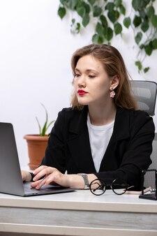 Una giovane donna attraente vista frontale in giacca nera e camicia bianca davanti al tavolo di lavoro con le tecnologie aziendali di lavoro portatile