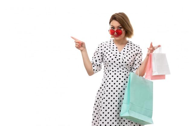 Una giovane donna bella vista frontale in abito bianco e nero a pois in occhiali da sole rossi che tengono i pacchetti di shopping in posa sorridente