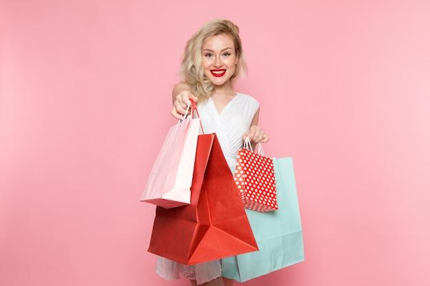 Una giovane donna bella vista frontale in abito bianco tenendo i pacchetti di shopping con il sorriso sul suo viso