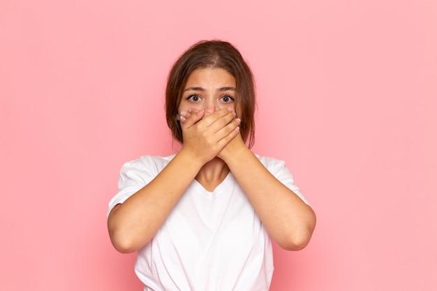 Una giovane donna bella vista frontale in camicia bianca che copre la bocca con espressione spaventata