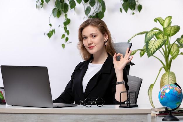 Una giovane donna bella vista frontale in camicia bianca e giacca nera, usando il suo computer portatile davanti al tavolo sorridente mostrando segno con foglie appese