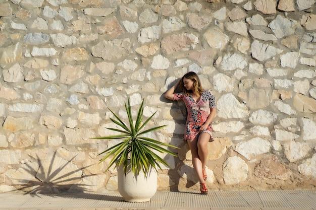Una giovane donna bellissima in un abito corto cammina per le strade di una piccola città europea.