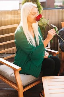 Una giovane donna bionda attraente che si siede sulla rosa odorante della rosa della sedia
