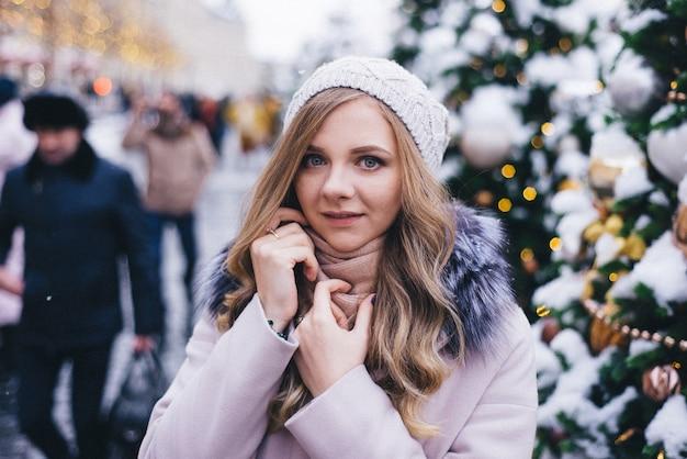 Una giovane donna cammina a natale nella piazza vicino agli alberi di natale decorati. candy è una lecca-lecca a forma di cuore.