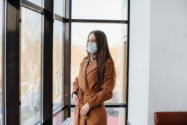 Una giovane donna cammina in una maschera durante la pandemia di coronovirus