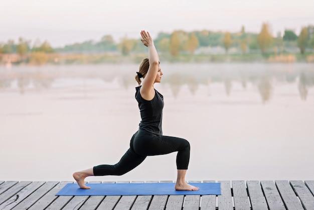 Una giovane donna caucasica di 36 anni pratica yoga all'aperto vicino a un fiume su un molo di legno al mattino