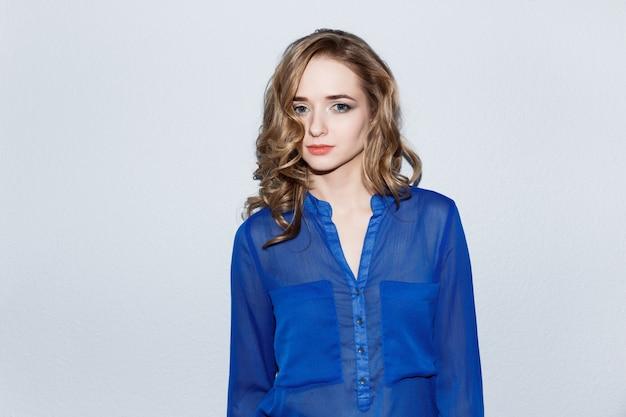 Una giovane donna caucasica piuttosto emotiva con il trucco in una camicia blu di fronte a un muro