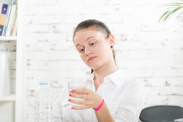 Una giovane donna che beve un bicchiere d'acqua