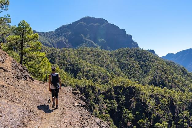 Una giovane donna che cammina sul trekking fino alla sommità della cumbrecita sul sentiero accanto alla caldera de taburiente motañas, isola di la palma, isole canarie, spagna