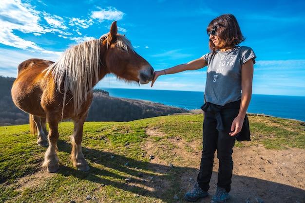 Una giovane donna che gioca con un cavallo libero dalla montagna di jaizkibel