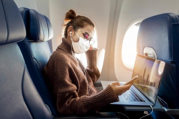 Una giovane donna che indossa la maschera sta viaggiando in aereo, nuovo viaggio normale dopo il concetto di pandemia covid-19