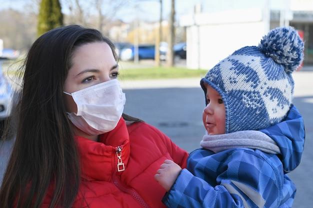 Una giovane donna che indossa una maschera e tiene in mano un bambino. misure protettive. madre e figlio in quarantena.