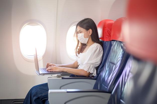 Una giovane donna che indossa una maschera per il viso sta usando il laptop a bordo, nuovo viaggio normale dopo il concetto di pandemia covid-19