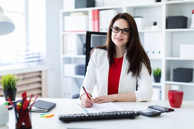 Una giovane donna che lavora in ufficio alla scrivania del computer. prima di mentire documenti.