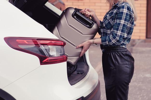 Una giovane donna che mette i suoi bagagli nel bagagliaio di un'auto