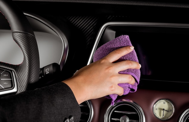 Una giovane donna che pulisce lo schermo dentro un'auto lussuosa