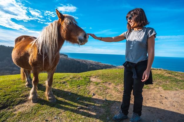 Una giovane donna che saluta un cavallo libero dalla montagna di jaizkibel vicino a san sebastian, gipuzkoa. spagna