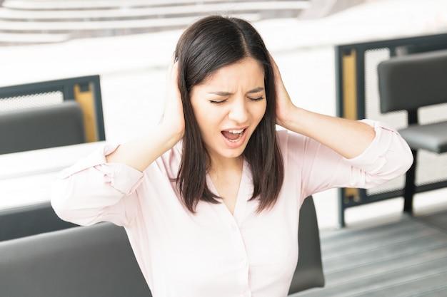 Una giovane donna che spara alle orecchie e urla, stanca di tutto.