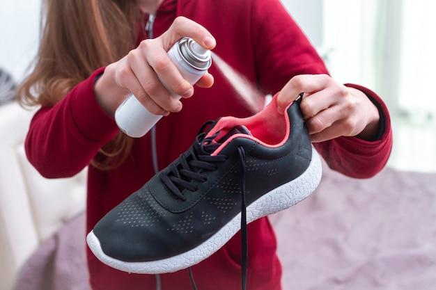 Una giovane donna che spruzza deodorante su scarpe da corsa sudate per eliminare l'odore sgradevole e cattivo. le calzature sportive necessitano di pulizia e rimozione degli odori.