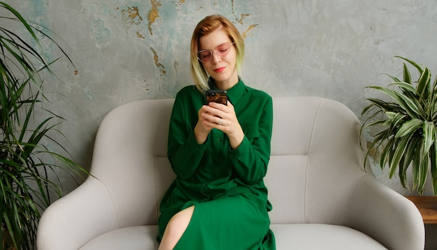 Una giovane donna che usa un telefono cellulare, manda un sms e gioca a giochi per cellulare. interni moderni ecologici a soppalco.