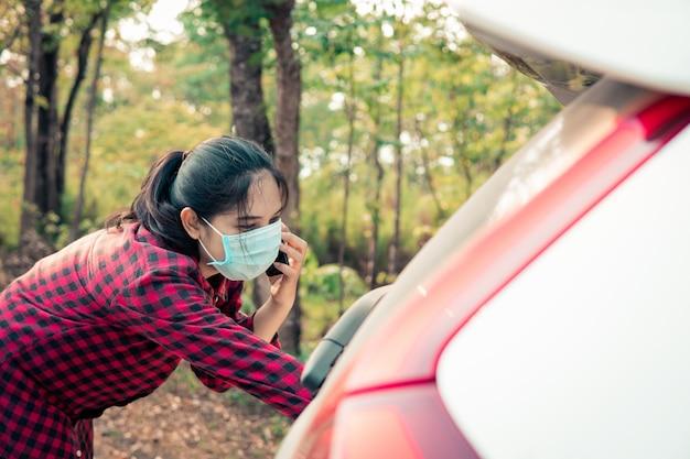 Una giovane donna chiama l'assicurazione mentre l'auto è rotta.