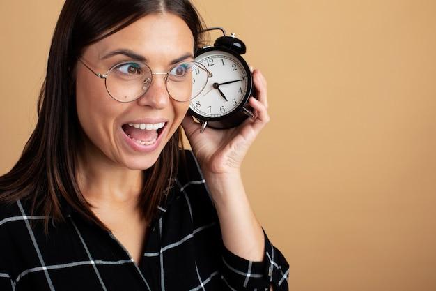 Una giovane donna con gli occhiali in possesso di una sveglia.