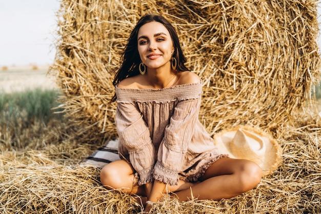 Una giovane donna con i capelli lunghi e in abito siede vicino a una balla di fieno. donna che posa sorridente e che esamina macchina fotografica