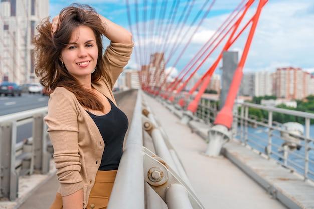 Una giovane donna con i capelli lunghi sta in piedi davanti al pittoresco ponte rosso di mosca