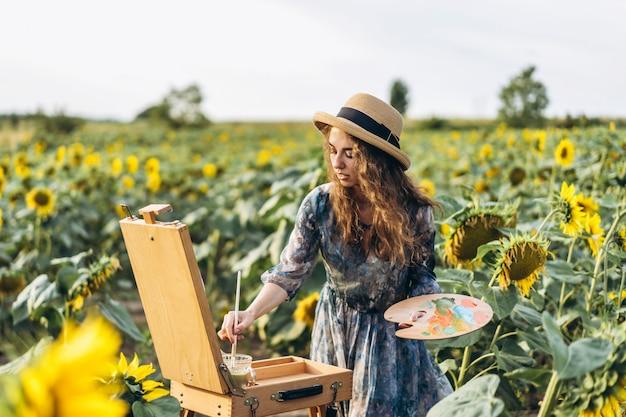 Una giovane donna con i capelli ricci e indossa un cappello sta dipingendo in natura. una donna si trova in un campo di girasoli in una bella giornata