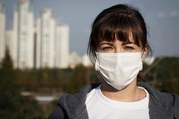 Una giovane donna con la maschera nella città, concetto di inquinamento atmosferico