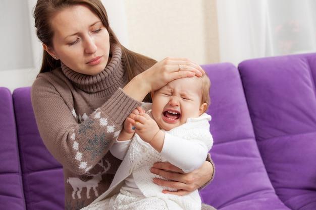 Una giovane donna con un bambino piangente malato