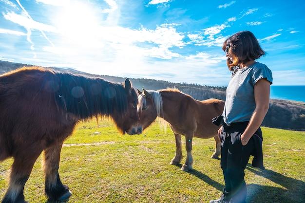 Una giovane donna con un cavallo libero dalla montagna di jaizkibel vicino a san sebastian, gipuzkoa. spagna