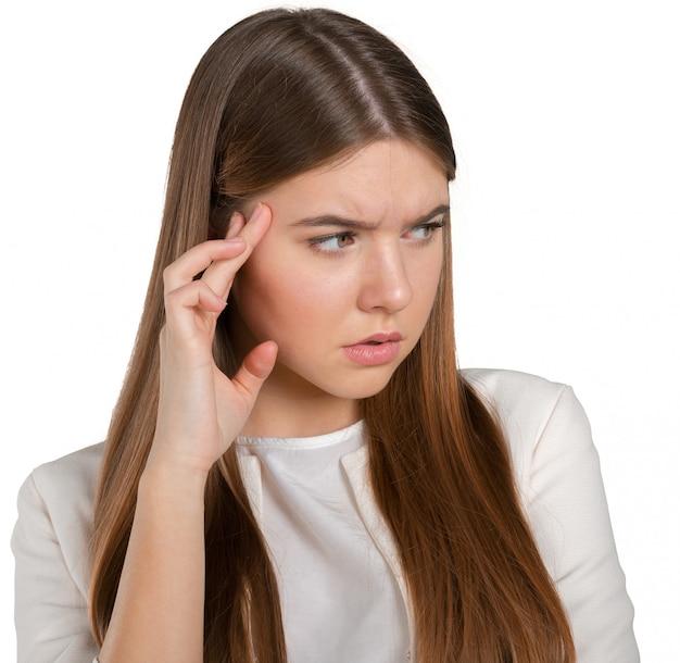Una giovane donna con un mal di testa che tiene la testa