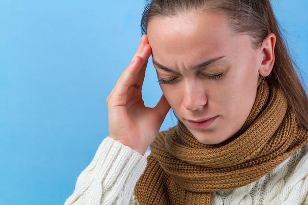 Una giovane donna con una sciarpa lavorata a maglia e un maglione caldo si sente male, ha mal di testa, emicrania