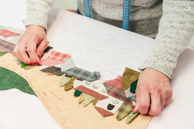 Una giovane donna creativa che crea paesaggi di rappezzatura del tessuto su carta