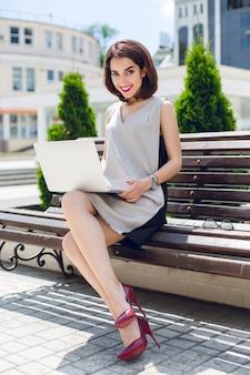 Una giovane donna d'affari piuttosto mora è seduta sulla panchina in città. indossa un abito grigio e nero e tacchi vinosi. sta scrivendo sul portatile e sorride alla telecamera.