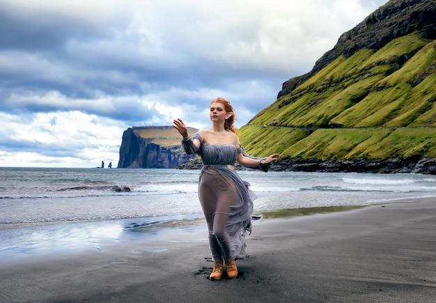 Una giovane donna dai capelli rossi vestita da elfo rimane sulla spiaggia con sabbia nera. isole faroe, danimarca