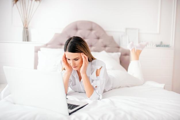 Una giovane donna di 25 anni di aspetto europeo giace su un letto con un laptop a casa su un letto bianco. sente mal di testa o affaticamento degli occhi, cattive notizie