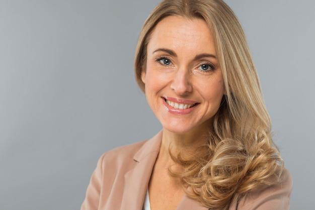 Una giovane donna di affari attraente che esamina macchina fotografica contro il contesto grigio