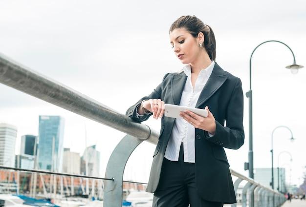Una giovane donna di affari che tiene telefono astuto che controlla il tempo sull'orologio