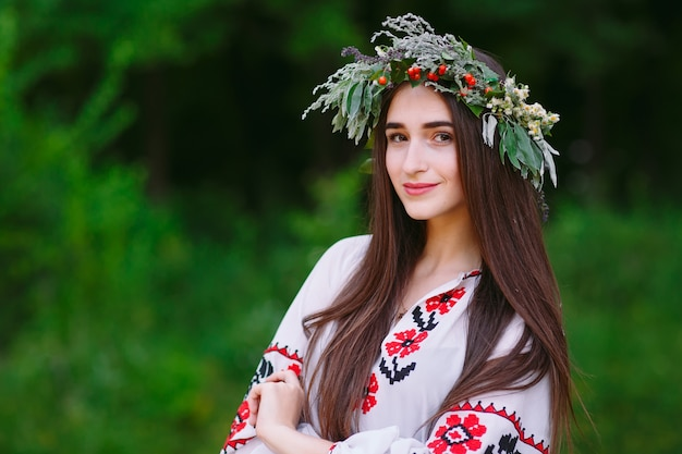Una giovane donna di aspetto slavo con una ghirlanda di fiori selvatici a metà estate.