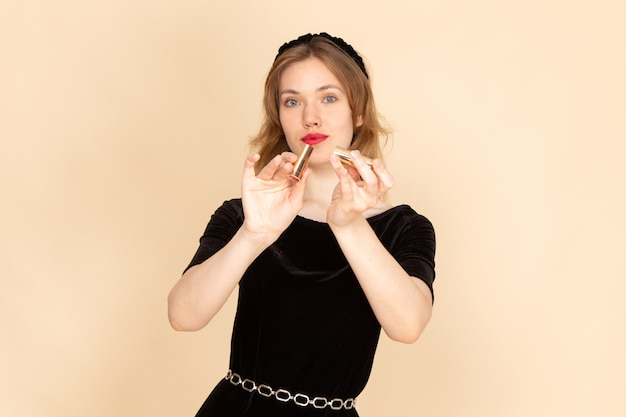 Una giovane donna di vista frontale in abito nero con cintura a catena che fa trucco sul beige