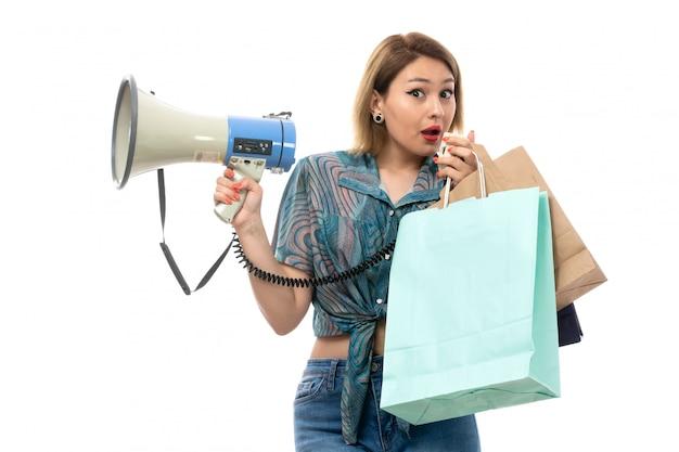 Una giovane donna di vista frontale in blue jeans colorati della blusa che tengono i pacchetti di acquisto facendo uso del megafono