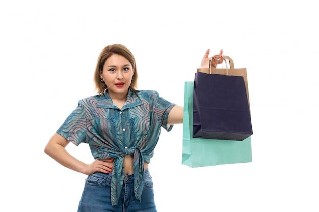 Una giovane donna di vista frontale in blue jeans colorati della blusa che tengono i pacchetti di acquisto