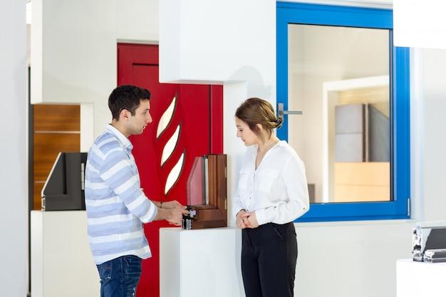 Una giovane donna di vista frontale in pantaloni bianchi della camicia bianca insieme al giovane che discute qualcosa durante l'attività di lavoro della costruzione di giorno