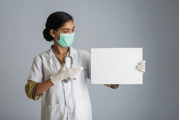 Una giovane donna dottore in una maschera medica con in mano un bordo bianco, il concetto di un'epidemia di coronavirus, covid-19.