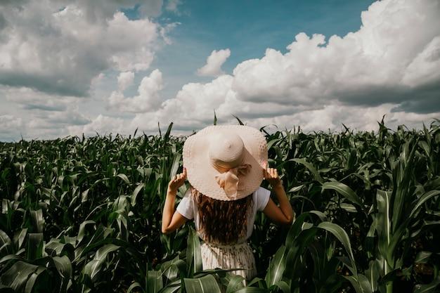 Una giovane donna è in piedi in un giardino tropicale guardando in lontananza tenendo il cappello con le mani