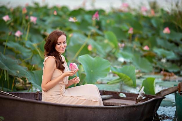 Una giovane donna è seduta in una barca su uno stagno con fiori di loto rosa