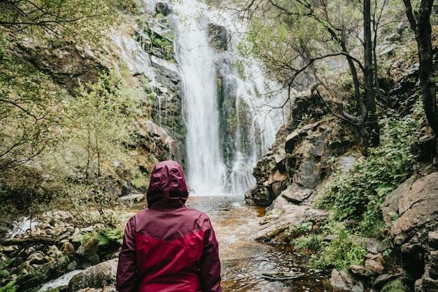 Una giovane donna escursionista davanti a una cascata