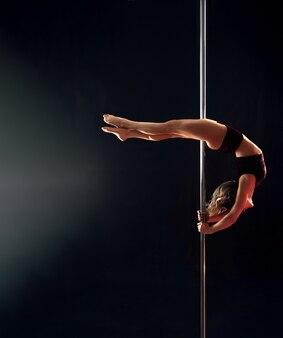 Una giovane donna esegue graziosi trucchi sul palo dopo aver girato la testa verso lo studio di danza, izolirovannoi in una stanza buia.